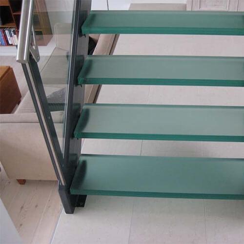 Glasværn og glastrin på malet ståltrappe